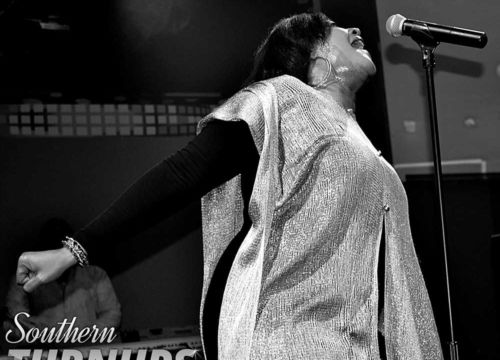 A professional shot of Keeshea Pratt on stage. Shot in black and white, capturing a side view of her singing intensely into a microphone on a stand.